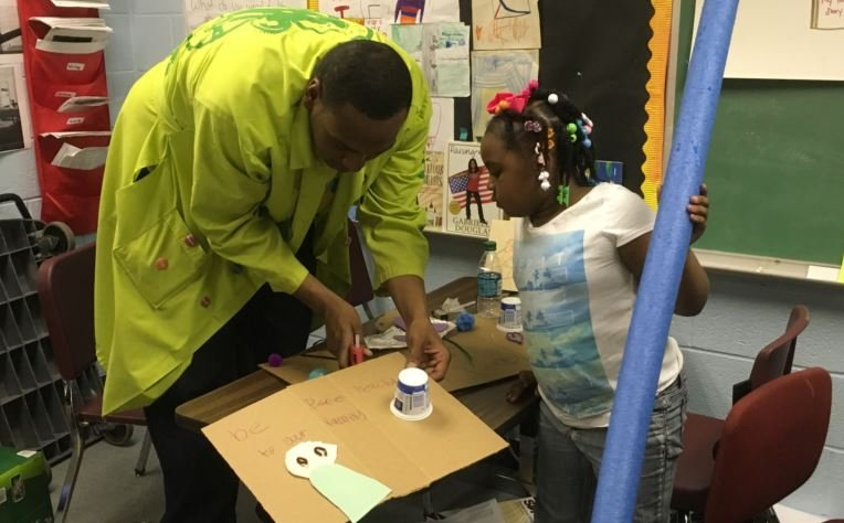 Jerald Smith with the Kentucky Science Center helps Sha'niya Philpot with a sign during class on Friday (Photo by Toni Konz, WDRB News)