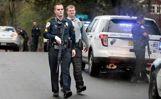 (Harry Lynch/The News & Observer via AP). In this Dec. 2, 2015 photo, University of North Carolina at Chapel Hill police officers stand down and return to their patrol cars after answering a second man with a rifle call adjacent to the school's cam...