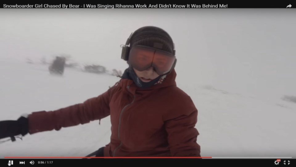 A bear supposedly chasing a snowboarder down a mountain