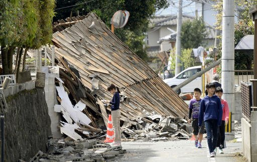 (Koji Harada/Kyodo News via AP). Children walk past a house collapsed by a magnitude-6.5 earthquake in Mashiki, Kumamoto prefecture, southern Japan, Friday, April 15, 2016.