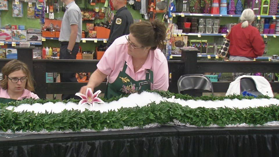 Crews work on the Garland of Lilies at the Middletown Kroger on Thursday.