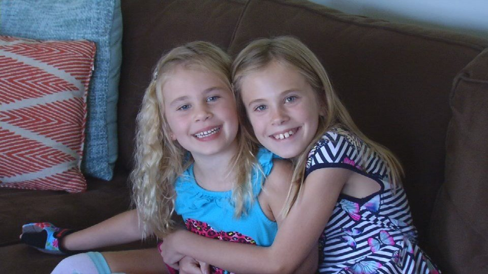Eden Hoelscher (left) is hugged by her older sister, Isabella