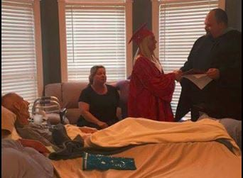 Bullitt East High senior Abigail Tucker is presented her diploma on Thursday night in front of her dying stepfather. Mike Underwood passed away early Friday morning. (Photo courtesy of Lisa Sheppard-Underwood)