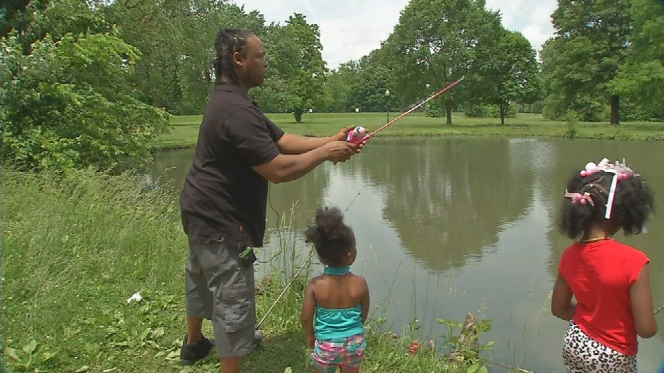 Kevin Richie teaches his daughters how to fish at Chickasaw Park