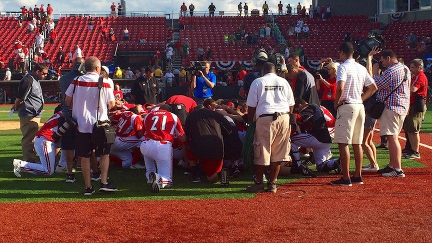 The University of Louisville baseball team kneels for a postgame prayer after winning its fourth straight regional championship. (WDRB photo by Eric Crawford)