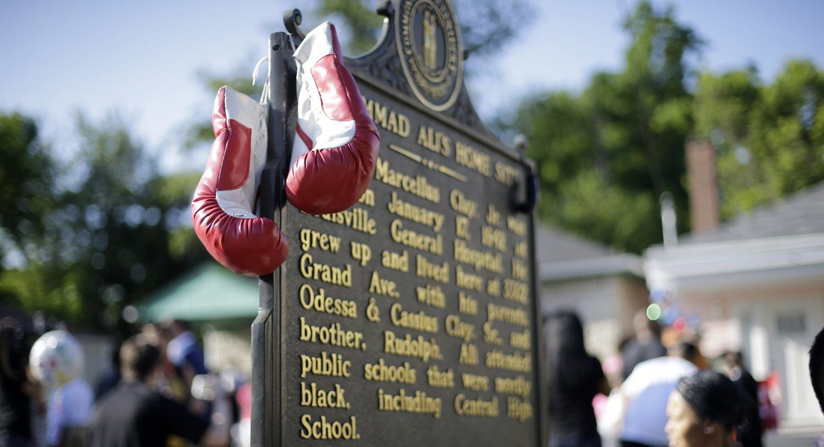 AP PHOTO: Boxing gloves hang on a plaque in front of the childhood home of Muhammad Ali.