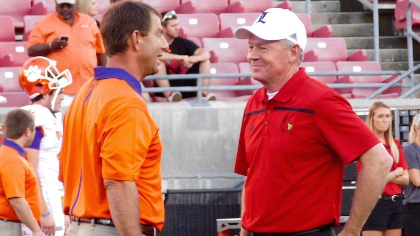 Dabo Swinney of Clemson (left) and Louisville's Bobby Petrino are ranked in the nation's top 12 college football coaches by Athlon Sports.
