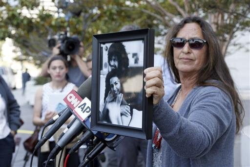 (AP Photo/Nick Ut). Janet Wolfe holds a photo of her brother Randy Wolfe, better known as Randy California, a member of the band Sprit outside federal court, Thursday, June 23, 2016 in Los Angeles.