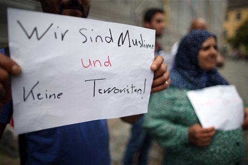 (Daniel Karmann/dpa via AP). Refugees from Syria stand near the site of the attack and hold up a sign reading 'we are Muslims and not terrorists' in Germany