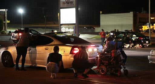 (Robert Cohen/St. Louis Post-Dispatch via AP). Protesters hide behind cars after shots were fired Tuesday, Aug. 9, 2016, in Ferguson, Mo., during a demonstration on the second anniversary of Michael Brown's death.