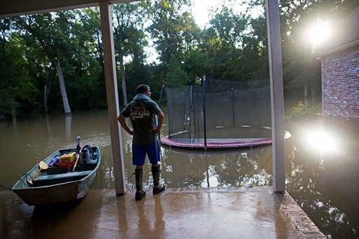 (AP Photo/Max Becherer). David Key looks at the back yard of his flooded home in Prairieville, La., Tuesday, Aug. 16, 2016. Key, an insurance adjuster, fled his home as the flood water was rising with his wife and three children.