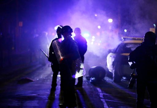 (AP Photo/Charlie Riedel, File). FILE - In this Nov. 25, 2014 file photo, police officers watch protesters as smoke fills the streets in Ferguson, Missouri.