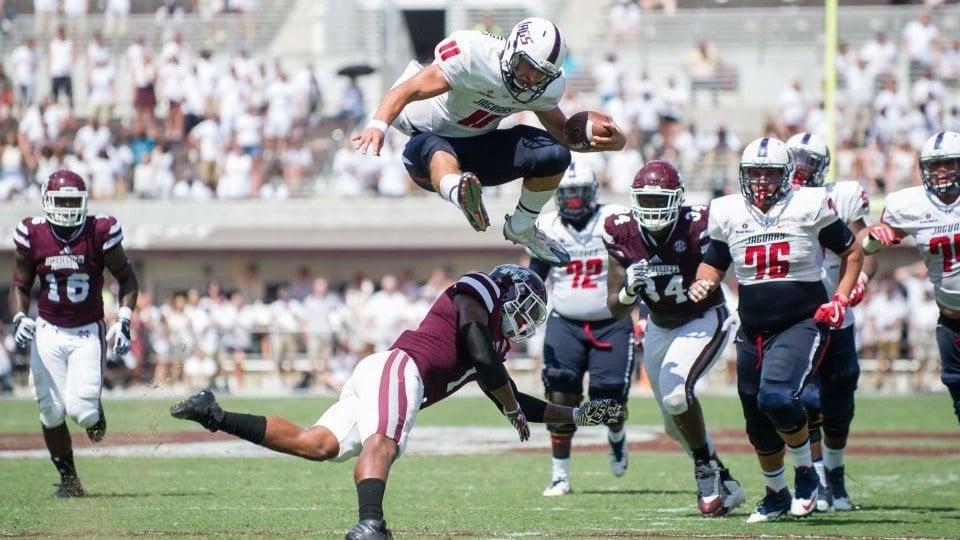 South Alabama quarterback Dallas Davis skies over a Mississippi State defender in a 21-20 upset win Saturday. (AP photo)
