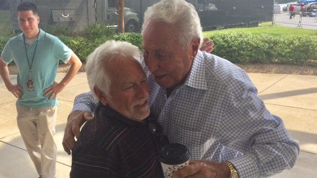 ESPN personality Lee Corso (right) hugs his friend Russ Brown, a local sports writer.