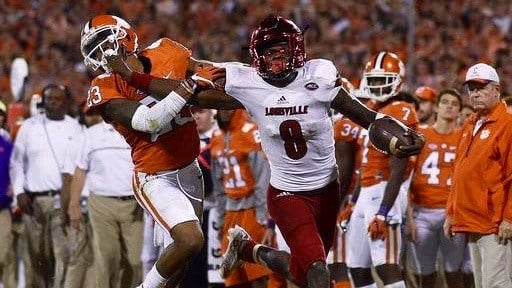 Louisville's Lamar Jackson uses a stiffarm to try to get free of a tackler. (AP photo)