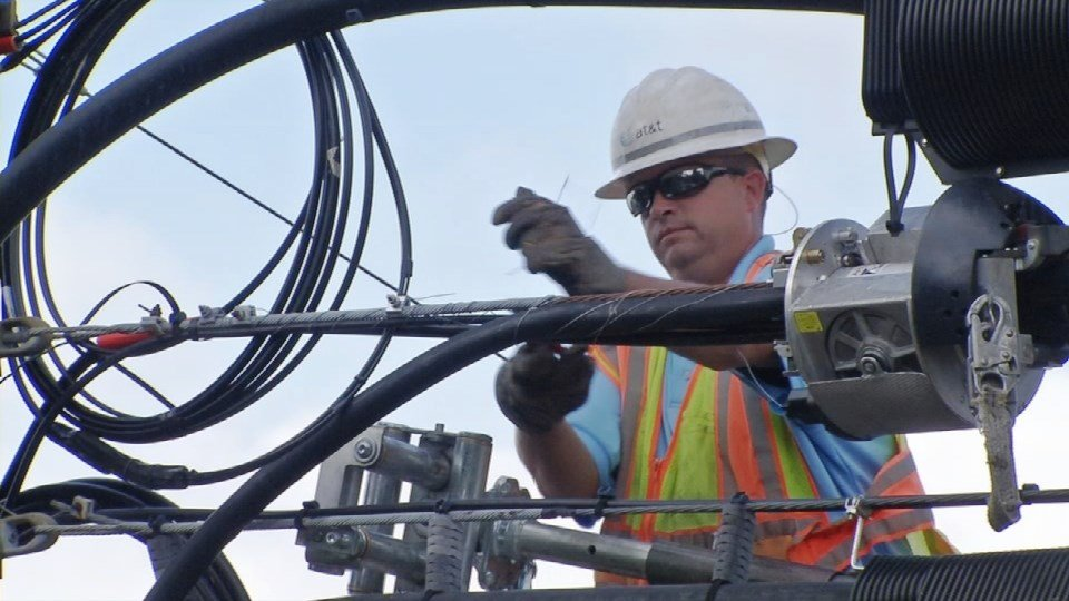 An AT&T worker installs fiber-optic cable off Goldsmith Lane in Louisville, Oct. 18, 2016.