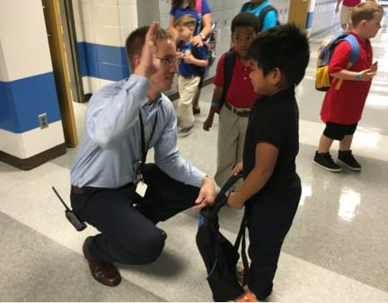 John Shanton gives second grader Nelson Limbu a high-five on the first day of school at Camp Taylor Elementary on Aug. 10, 2016 (Photo by Toni Konz, WDRB)