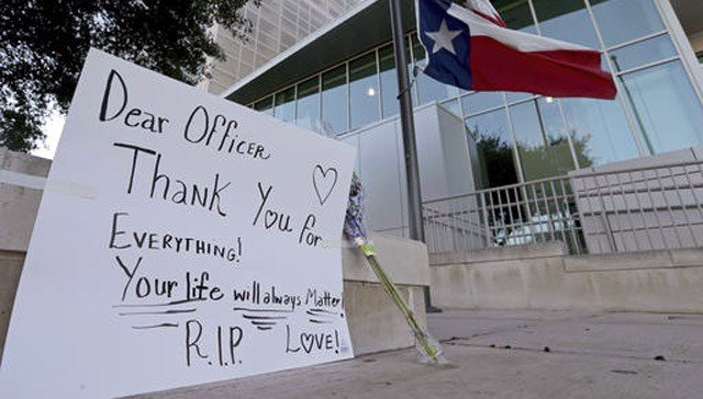 (Edward A. Ornelas/The San Antonio Express-News via AP). An American flag and a Texas state flag fly at half-staff at San Antonio Police Department headquarters near a sign and flowers left by Lucy Aldaba after Det. Benjamin Marconi was fatally shot.