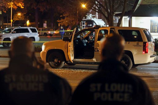 "(David Carson/St. Louis Post-Dispatch via AP). Police investigate a scene after a St. Louis police officer was shot in what the police chief called an ""ambush"" on Sunday, Nov. 20, 2016, in St. Louis."
