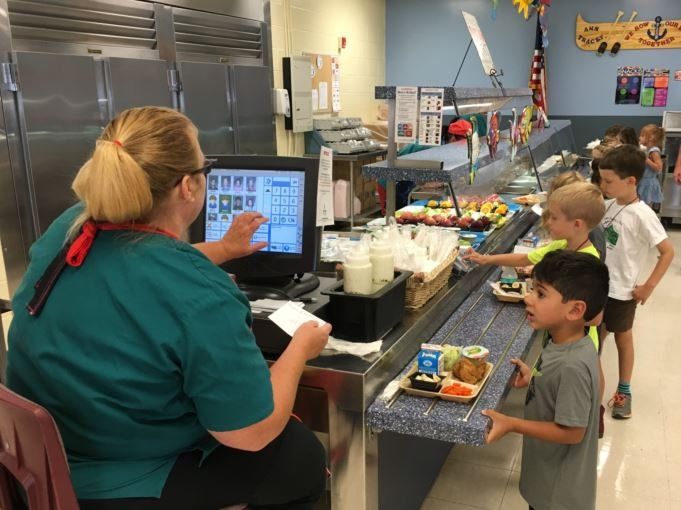 A school nutrition worker helps students at Bloom Elementary School on the first day of school, Aug. 10, 2016. (Photo by Toni Konz, WDRB)