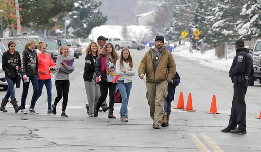 (AP Photo/Rick Bowmer). A police officer escorts students down the street following a school lockdown at Mueller Park Junior High after a student fired a gun into the ceiling Thursday, Dec. 1, 2016, in Bountiful, Utah.