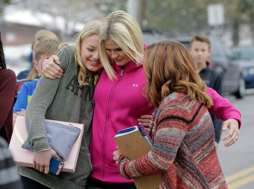 (AP Photo/Rick Bowmer). A mother greets her daughter and a friend following a lockdown at Mueller Park Junior High after a student fired a gun into the ceiling Thursday, Dec. 1, 2016, in Bountiful, Utah.