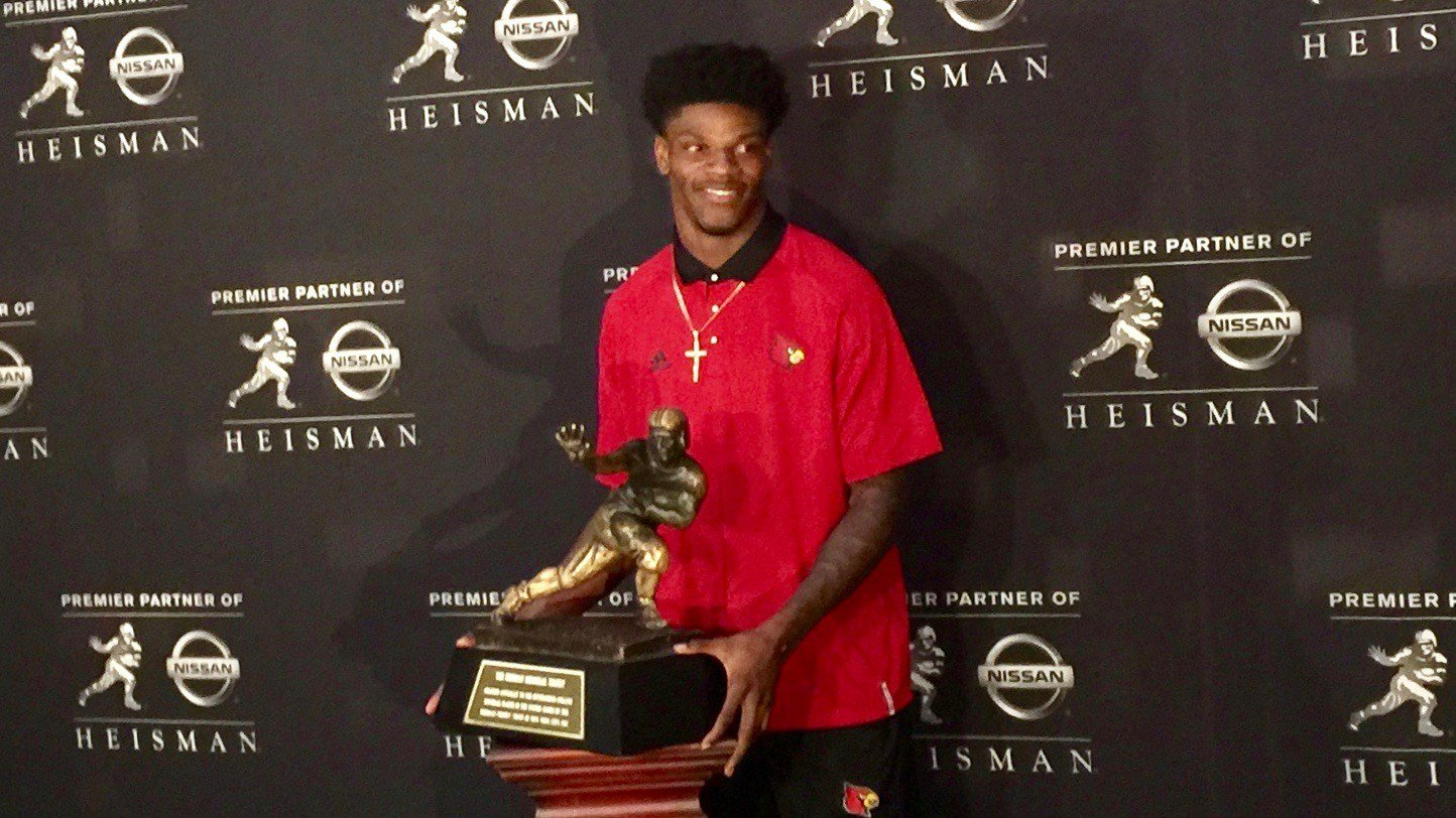 Louisville quarterback Lamar Jackson poses with the Heisman Trophy during his New York media session Friday. (WDRB photo by Eric Crawford)