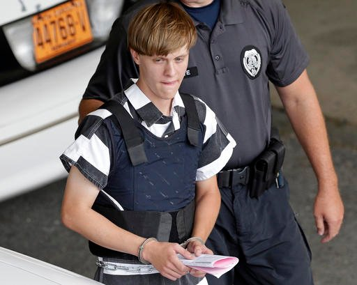 (AP Photo/Chuck Burton, File). FILE - In this June 18, 2015 file photo, Charleston, S.C., shooting suspect Dylann Storm Roof is escorted from the Cleveland County Courthouse in Shelby, N.C.