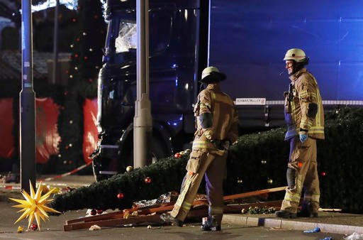 (AP Photo/Markus Schreiber). Police officers inspect the crime scene in Berlin, Germany, Tuesday, Dec. 20, 2016, the day after a truck ran into a crowded Christmas market and killed several people.