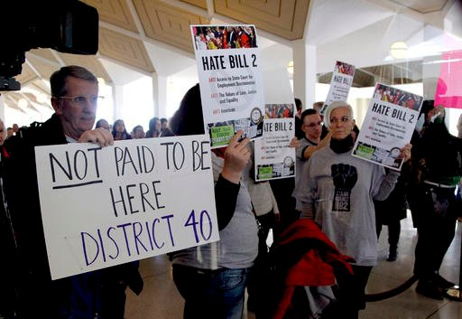 (Chris Seward/The News & Observer via AP). Opponents of HB2 hold signs outside the North Carolina House chambers gallery as the North Carolina General Assembly convenes for a special session at the Legislative Building in Raleigh, N.C.