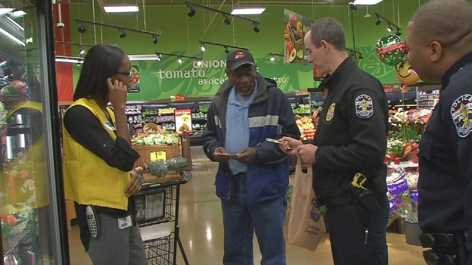 An LMPD officer surprises a customer with a free card at the Kroger store on 27th and Broadway.