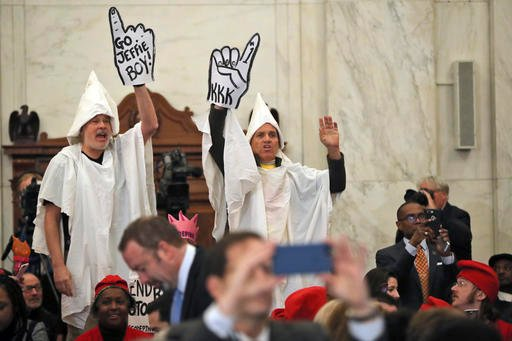 (AP Photo/Andrew Harnik). Demonstrators are seen on Capitol Hill in Washington, Tuesday, Jan. 10, 2017, during the Senate Judiciary Committee's confirmation hearing for Attorney General-designate, Sen. Jeff Sessions, R-Ala.