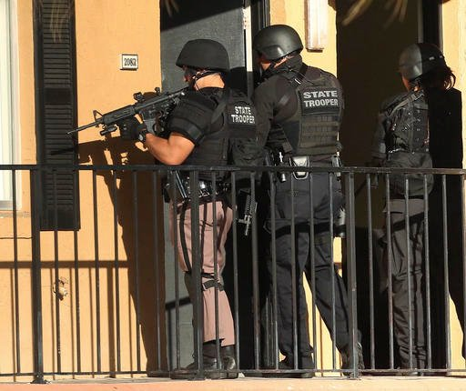 (Stephen M. Dowell/Orlando Sentinel via AP). Law enforcement officers conduct a door-to-door search at an apartment complex in Orlando, Fla., Monday, Jan. 9, 2017.