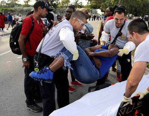 (Carl Juste/Miami Herald via AP). Miami-Dade Fire and Rescue paramedics lift a woman after she lost consciousness after several were injured in a shooting at Martin Luther King Jr. Memorial Park in Miami-Dade, Fla., Monday, Jan. 16, 2017.