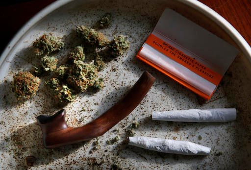 (AP Photo/Robert F. Bukaty, File). FILE - This this Nov. 21, 2014, file photo shows medical marijuana, a pipe, rolling papers and two joints in Belfast, Maine.