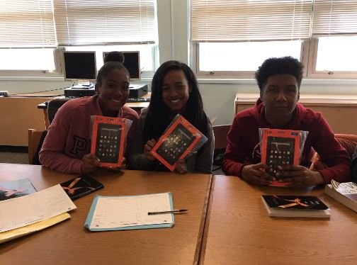 Three Central High sophomores hold up the tablets given to them by a local couple on Thursday. (Photo by Toni Konz, WDRB News)