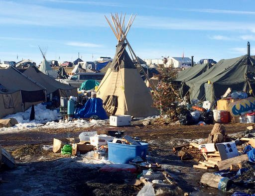 In this Thursday, Feb. 16, 2017, photo, debris is piled on the ground awaiting pickup by cleanup crews at the Dakota Access oil pipeline protest camp in southern North Dakota near Cannon Ball.