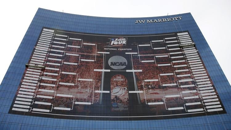 Workers add team names to a giant NCAA bracket in 2015 in Indianapolis. (AP photo)