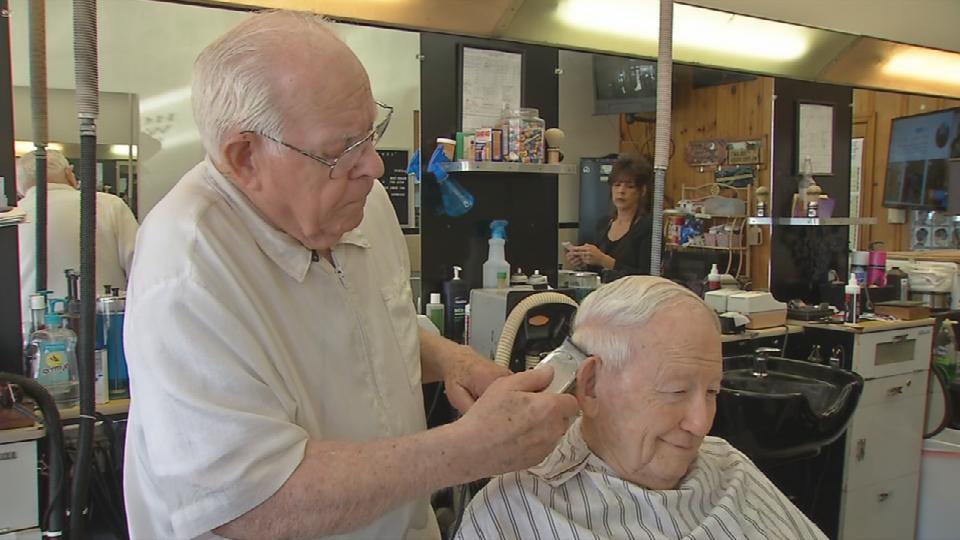 Leon Wingfield cuts a regular customer's hair at his barber shop on Cane Run Road.