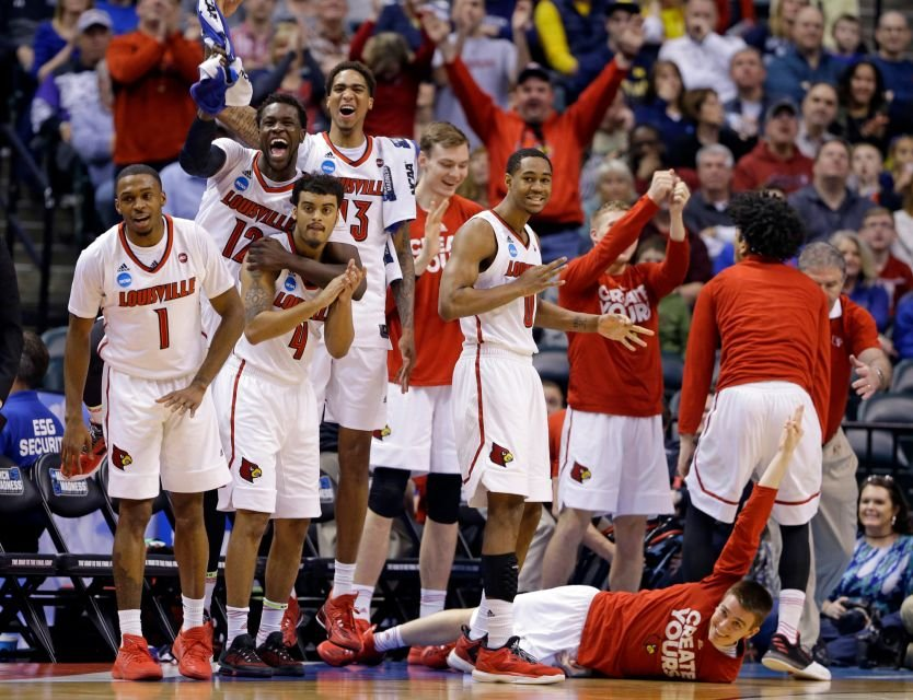 Happier times: Louisville's bench enjoys a dunk by Deng Adel in the first half. (AP photo by Michael Conroy)