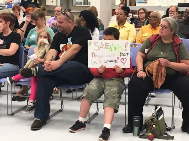 A Maupin student held a sign as parents addressed the JCPS school board on Tuesday about the Catalpa program. (Photo by Toni Konz, WDRB News)