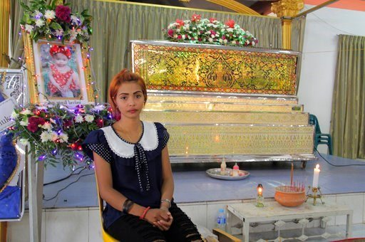(AP Photo). Chiranut Trairat, mother of an 11-month-old baby girl, sits in front of her daughter's coffin at Si Sunthon temple in Phuket, Thailand, Wednesday, April 26, 2017. Her husband was upset with her hanged their daughter on Facebook Live.
