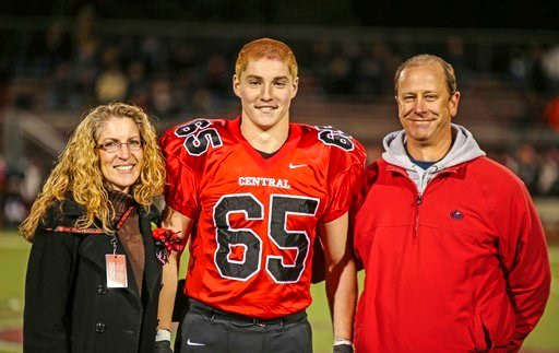 """(Patrick Carns via AP). This Oct. 31, 2014, file photo provided by Patrick Carns shows Timothy Piazza, center, with his parents Evelyn Piazza, left, and James Piazza, right, during Hunterdon Central Regional High School football's """"Senior Night"""""""