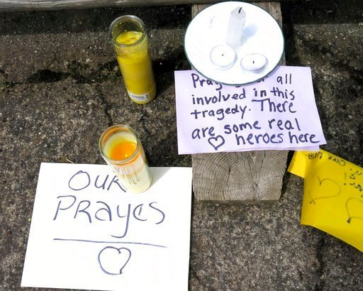 (AP Photo/Gillian Flaccus). Well-wishing messages and candles for an injured employee are shown outside a grocery store in Estacada, Ore., Monday, May 15, 2017.