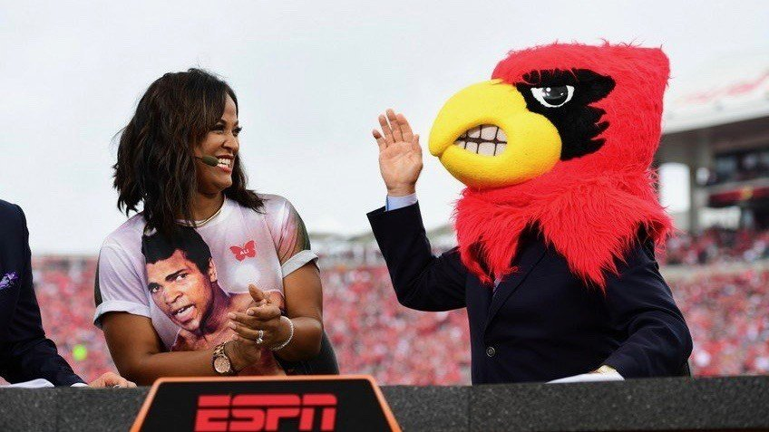 Lee Corso, next to Laila Ali, made the right pick before Louisville's game against Florida State. Eric Crawford writes that ESPN made the right call retaining him for College GameDay. (ESPN PR photo).