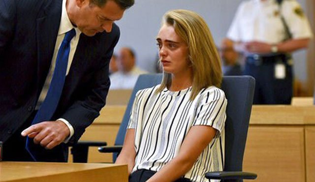(Faith Ninivaggi/The Boston Herald via AP, Pool). Attorney Joseph Cataldo talks to his client, Michelle Carter, before meeting at a side bar at the beginning of the court session at Taunton Juvenile Court in Taunton, Mass., on Monday, June 5, 2017.