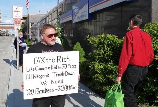 (Derik Holtmann/Belleville News-Democrat, via AP). FILE - In this April 17, 2012, photo, James Hodgkinson of Belleville protests outside of the United States Post Office in Downtown Belleville, Ill.