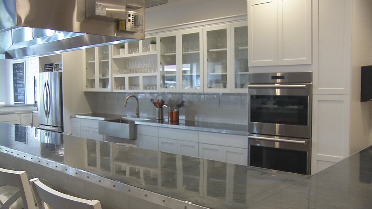 Guests will be seated around a table watching chefs cook in a residential style kitchen.