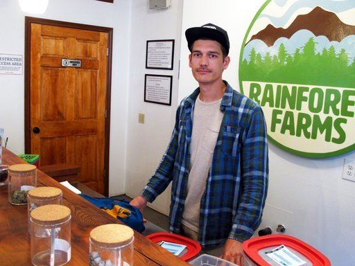 (AP Photo/Becky Bohrer). James Barrett, a co-owner of Rainforest Farms, poses in his retail marijuana shop in Juneau, Alaska.