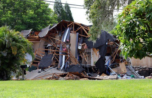 Alessandra da Pra/Tampa Bay Times via AP). Debris is strewn about from a partially collapsed home in Land O' Lakes, Fla. on Friday, July 14, 2017.A sinkhole that started out the size of a small swimming pool and grew until it swallowed the home.